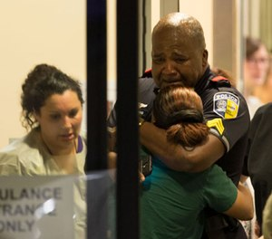 A Dallas Area Rapid Transit police officer receives comfort at the Baylor University Hospital emergency room entrance Thursday, July 7, 2016, in Dallas. (AP Image)