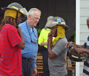 Philanthropist Ian Edgar (center) has thrown financial and political clout at getting a fire department established on Exuma. Below, IFRM volunteers select proper fitting gear for the new firefighters. (Photo: Rick Markley)