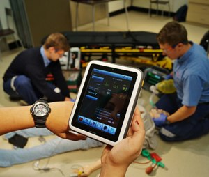 Close-up of watch and tablet screen during a simulation debriefing. (Image Rafi Uddin)