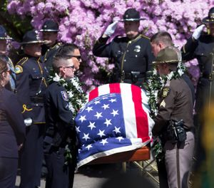 An honor guard carries the casket of Cowlitz County Deputy Justin DeRosier as a procession makes its way to the Chiles Center at the University of Portland, where a memorial service is taking place for the slain deputy, Wednesday, April 24, 2019 in Portland, Ore. (Beth Nakamura/The Oregonian via AP)