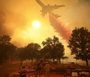 A 747 Global Airtanker makes a drop in front of advancing flames from a wildfire. (Photo/AP)