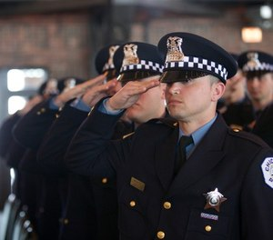 Police recruits salute during the playing of the National Anthem at the Chicago Police Department recruit graduation ceremony at Chicago's Navy Pier Grand Ballroom March 30. Four Illinois National Guard Soldiers were among the 107 recruits that graduated, dedicating themselves to serving the community and the city of Chicago. (U.S. Army National Guard photo by Spc. Jason Dorsey, Illinois National Guard Public Affairs)