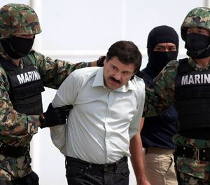"""Joaquin """"El Chapo"""" Guzman, center, is escorted to a helicopter in handcuffs by Mexican navy marines at a hanger in Mexico City, after he was captured overnight in the beach resort town of Mazatlan.  (AP Photo/Eduardo Verdugo, File)"""