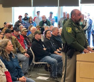 """An overflowing crowd packs the Elko County Commission chamber as Elko County Sheriff Aitor Narvaiza presents his case for the county to declare a """"Second Amendment sanctuary"""" in Elko, Nev (Tim Burmeister/Elko Daily Free Press via AP, File)"""