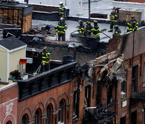 FDNY firefighters work on rooftops in the aftermath of a fatal apartment building fire on the Upper East Side in New York, Thursday, Oct. 27, 2016. (AP Photo/Craig Ruttle)