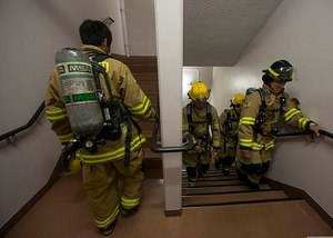 Firefighters running stairs in PPE replicates aerobic capacity requirements of NFPA 1582 (Photo/Wikimedia Commons)