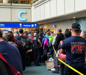 "People wait to get through security at the Orlando International Airport following a security incident on Saturday, Feb. 2, 2019. Passengers on shuttles to gates at Florida's busiest airport had to be brought back for a second screening, bringing security checkpoints to a temporary standstill. A spokeswoman for Orlando International Airport told television station WKMG on Saturday that the passengers were returned in ""an abundance of caution"" after some passengers may have gotten through the checkpoints without being screened property. (Jonathan Hayward/The Canadian Press via AP)"
