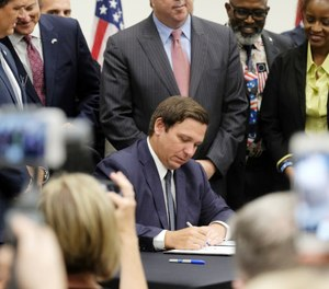 Florida Gov. Ron DeSantis signs the Sanctuary City bill Friday, June 14, 2019 at the Okaloosa County, Fla., Commission Chambers in Shalimar Fla. (Michael Snyder/Northwest Florida Daily News via AP)
