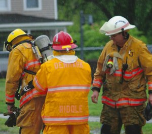 Denmark Fire & Rescue Chief Todd Ross, right, wears a thin pink band on his helmet to remember Bob Riddle, a founding member of the volunteer department who died of brain cancer. (courtesy image)