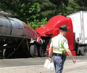 A Georgia state trooper works the scene of a deadly crash in which five people died and three others were injured early Wednesday, April 22, 2015, in Ellabelle, Ga., west of Savannah. The Georgia State Patrol said seven total vehicles, including two tractor trailers, were involved in the early morning collision on Interstate 16 about 20 miles west of Savannah. (AP Photo/Russ Bynum)