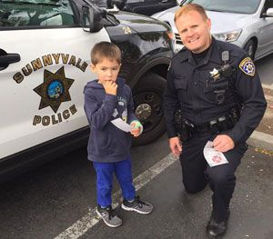 Officer Ben Holt of the Sunnyvale (Calif.) Police Department kneels next to Hunter, a boy whose special needs created an opportunity for law enforcement to shine as brightly as it does thousands of times a day across America. (Image Courtesy of Corinne Oestreich)