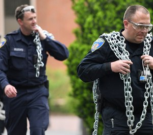 Baltimore Police carry chains that protesters had used during a monthlong sit-in at Garland Hall on Johns Hopkins' Homewood campus, Wednesday, May 8, 2019. (Jerry Jackson/The Baltimore Sun via AP)