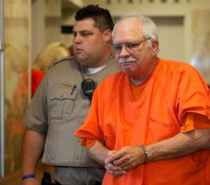 In this May 31, 2016 file photo, Robert Bates, a former Oklahoma volunteer sheriff's deputy who said he mistook his handgun for his stun gun when he fatally shot an unarmed suspect in 2015, is escorted from the courtroom following his sentencing at the courthouse in Tulsa, Okla. (AP Photo/Sue Ogrocki, File)