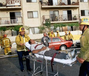 In this May 3, 1993, file photo, a survivor of an apartment complex fire is wheeled to an ambulance by Los Angeles Fire Department personnel near downtown Los Angeles. (AP Photo/Doug Pizac,File)