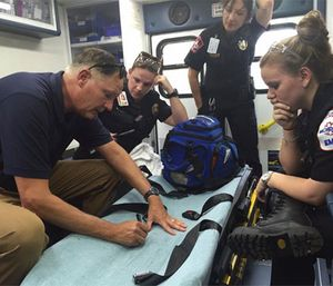 Dr. Rob Dickson and MCHD personnel review a call, using an ambulance as a mobile classroom. (Facebook MCHD)