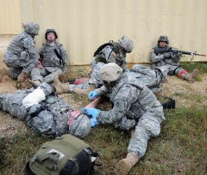 Combat medics treat simulated injured infantry soldiers during a firefight in a village at a Mobile Urban Training Site at Fort McCoy, Wis. The medics had removed the injured soldiers from the line of fire to stabilize them before evacuation. The training was part of pre-deployment medic training. (Image Tom Michele)