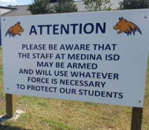 """In notifying the community that the school district was allowing teachers and staff to be armed, a school in Texas took a straightforward approach with a giant sign reading, """"Attention, please be aware that the staff at Medina ISD may be armed and will use whatever force is necessary to protect our students."""" (AP Image)"""