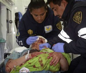A paramedic holds the hands of a newborn as his colleague attends to the baby's mother, who was evacuated from the maternity and children's hospital in Cuajimalpa, on the outskirts of Mexico City, Thursday, Jan. 29, 2015. The woman give birth to her baby in the ambulance after a powerful gas tank truck explosion shattered the maternity and children's hospital on the western edge of Mexico's capital, killing at least three adults and one baby and injuring dozens. (AP Photo)