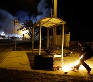 A man with a Molotov Cocktail prepares to throw it at a line of police officers in the distance in Ferguson (Mo.) during rioting in August 2014. (AP Photo/Jeff Roberson)