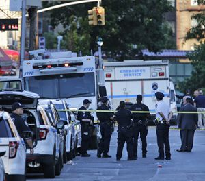 Emergency personnel stand near the scene where a police officer was fatally shot while sitting in a marked vehicle in the Bronx section of New York, Wednesday, July 5, 2017. Police said Officer Miosotis Familia died at a hospital early Wednesday. (AP Photo/Seth Wenig)