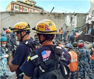 In this May 12, photo provided by the U.S. Agency for International Development, Los Angeles County Fire Department urban search and rescue team memebrs work to recover survivors from a four-story building that collapsed in this week's earthquake in Singati, a mountain village in Nepal. (Kashish Das/USAID/via AP)
