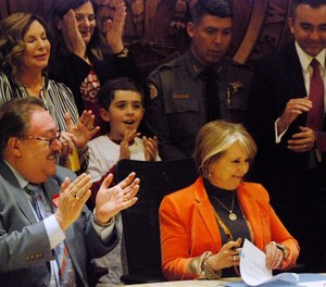 Democratic New Mexico Gov. Michelle Lujan Grisham, sitting right, signs a bill into law that expands background checks to nearly all gun sales in New Mexico in a ceremony in in Santa Fe, N.M. (AP Photo/Morgan Lee)