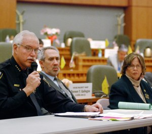Mike Heal, left, police chief for the city of Aztec, N.M., testifies in support of a state bill that would take away guns temporarily under court orders from people who are considered a danger to themselves or others, in Santa Fe, N.M. Heal says the bill from Democratic state Reps. Daymon Ely, center, and Joy Garratt, right, provides a new tool to keep school students safe. (AP Photo/Morgan Lee)