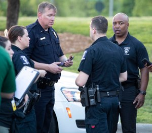 People gather across from the campus of UNC Charlotte after a shooting incident at the school Tuesday, April 30, 2019, in Charlotte, N.C. (AP Photo/Jason E. Miczek)