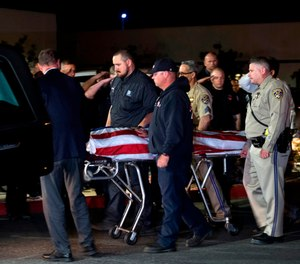 In this Saturday, April 6, 2019 photo, officers escort the remains of fallen California Highway Patrol Sgt. Steve Licon's as it is transferred from the Inland Valley Medical Center to the Perris Coroner in Wildomar, Calif.