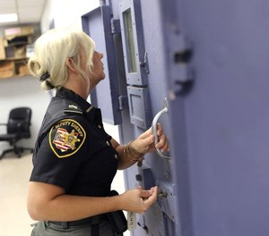 Franklin County Sheriff's Sgt. Mandy Rennie checks on an inmate in a cell in the Franklin County Corrections Center in Downtown Columbus. (Brooke LaValley/Dispatch)