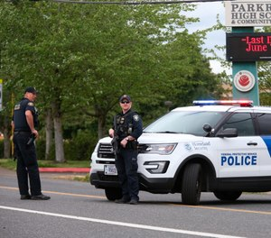 Police are positioned outside Parkrose High School Parkrose High School during a lockdown after a man armed with a gun was wrestled to the ground by a staff member (Dave Killen/The Oregonian via AP)
