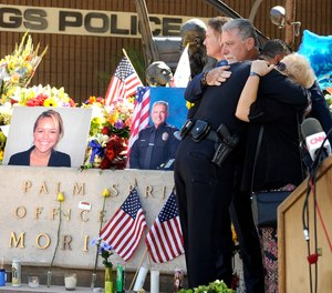 "Palm Springs councilmembers Ginny Foat, far right and J.R. Roberts, hug Palm Springs Police Chief Bryan Reyes at the conclusion of a press conference for slain Palm Springs Police Officers Jose ""Gil"" Gilbert Vega and Lesley Zerebny (AP Photo/Rodrigo Pena)"