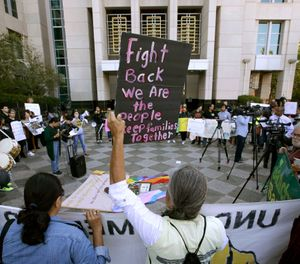 Protesters demonstrate outside the federal courthouse in Sacramento, Calif., where a judge heard arguments over the U.S. Justice Department's request to block three California laws that extend protections to people in the country illegally. (AP Photo/Rich Pedroncelli, File)