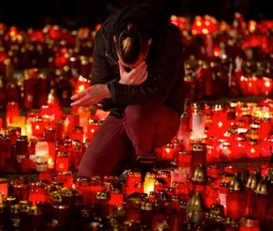 A man touches his forehead holding a candle outside the Colectiv nightclub in Bucharest, Romania, Friday, as people mark one week since a deadly fire started during a concert. (AP Photo/Vadim Ghirda)