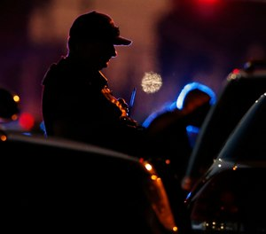 A law enforcement officer mans a barricade near a home that authorities have surrounded where an armed suspect has taken refuge after shooting a Sacramento police officer, Wednesday, June 19, 2019, in Sacramento, Calif. (AP Photo/Rich Pedroncelli)