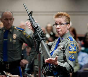 Detective Barbara J. Mattson, of the Connecticut State Police, holds a Bushmaster AR-15 rifle, the same make and model used by Adam Lanza in the 2012 Sandy Hook School shooting (AP Photo/Jessica Hill, File)