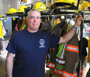 In this Nov. 4, 2016 photo, Scott Geiselhart stands next to turnout gear at the Frazee Fire Department fire hall in Frazee, Minn.  (AP Photo/Kevin Cederstrom)