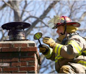 A Lancaster, Mass., firefighter operates at a chimney fire (Photo Scott LaPrade).