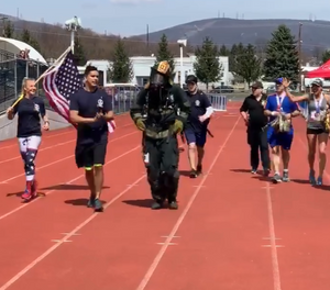 Upon crossing the finish line, firefighter Ryan Robeson was swarmed by medical personnel, who quickly removed his gear and gave him water, Gatorade and cold towels. (Photo/Screenshot)