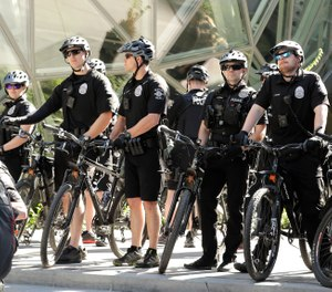 Seattle Police officers on bikes stand in front of the Amazon Spheres during a march for immigrant and workers rights on May Day in downtown Seattle. (AP Photo/Ted S. Warren, File)