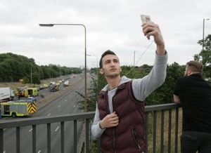 Man taking a selfie in front of a motor vehicle collision (Photo Twitter @DailyMirror)