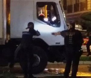 Police shine a light into the cab as they approach the truck that plowed through revelers gathered for Bastille Day fireworks in Nice, killing at least 84 people. (NADER EL SHAFEI via AP) MANDATORY CREDIT
