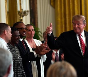 President Donald Trump gestures to Troy Powell, left, at the 2019 Prison Reform Summit and First Step Act Celebration in the East Room of the White House in Washington, April 1, 2019. (AP Photo/Susan Walsh)