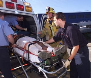 An American Medical Response paramedic, right, and a Ventura County firefighter help an injured man. (Bryan Chan/Los Angeles Times/TNS)