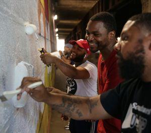 "Russell Craig, center, works with Guild painters on ""Tunnel Vision: A Journey Through Color,"" by Brad Carney, in the Belgrade tunnel between Lehigh Avenue and Somerset Street."