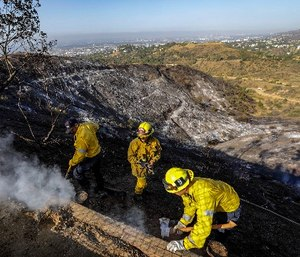 Firefighters take care of smoldering wood on a hillside along the road leading to Griffith Observatory on Wednesday July 11, 2018, in Los Angeles. (Irfan Khan/Los Angeles Times/TNS)