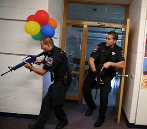 Two police officers carry blank weapons as they participate in an active shooter exercise with police, emergency workers, teachers and administrators on September 12, 2015, at Oak Knoll School in Cary, Ill. (Anthony Souffle/Chicago Tribune/TNS)