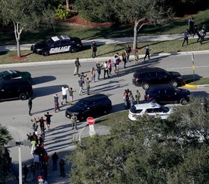 Students are evacuated by police out of Stoneman Douglas High School in Parkland, Fla., after a shooting on Wednesday, Feb. 14, 2018. (Mike Stocker/Sun Sentinel/TNS)