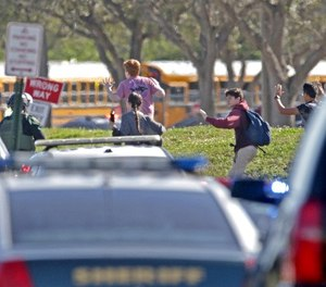 Students run wth their hands in the air outside of Stoneman Douglas High School in Parkland, Fla. after reports of an active shooter on Wednesday, Feb. 14, 2018. (John McCall/Sun Sentinel/TNS)