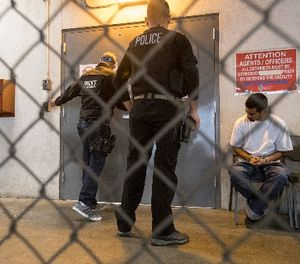 23-year-old Juan Vega, right, sits on a bench as agents unlock a door to take him inside for processing at the ICE downtown staging facility in on April 18, 2017 in Los Angeles. (Brian van der Brug/Los Angeles Times/TNS)
